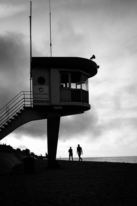 Silhouettes under the lifeguard station ~ Lion-sur-Mer, Normandy. ©Valérie Jardin